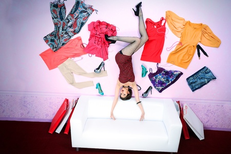 Charming fashionable woman flying in the room, surrounded by lots of her clothes. photo