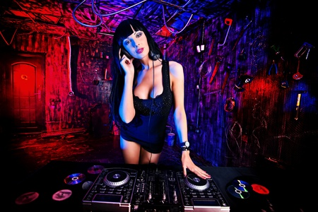 Beautiful sexy DJ girl working on a party in the old garage. Stock Photo - 21371854