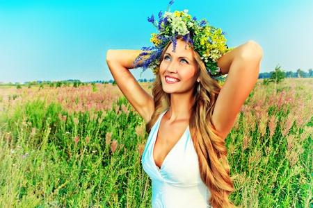 Portrait of a romantic smiling young woman in a circlet of flowers outdoors. photo
