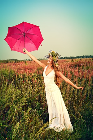 woman umbrella: Romantic smiling young woman in light summer dress standing in the meadow with umbrella.