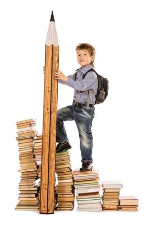 subiendo escaleras: Un niño que sube las escaleras de los libros con un enorme lápiz. Educación. Aislado en blanco. Foto de archivo