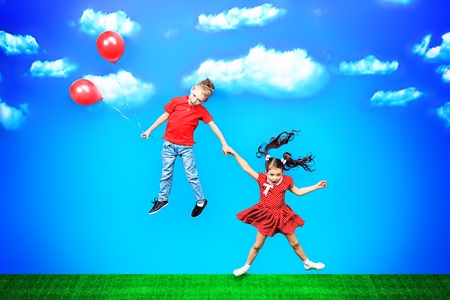flying man: Two happy children flying together on balloons in a bright summer day.
