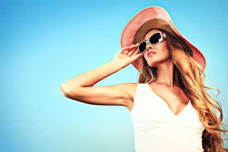 elegant woman: Joven y bella mujer con sombrero y gafas de sol posando en el cielo elegante.