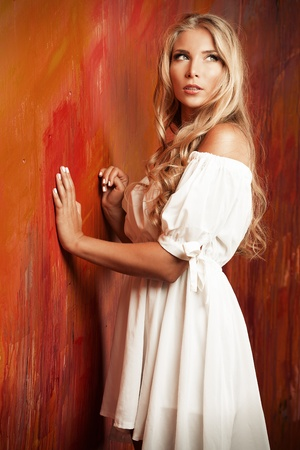 Charming blonde girl in romantic white dress over vivid background. photo