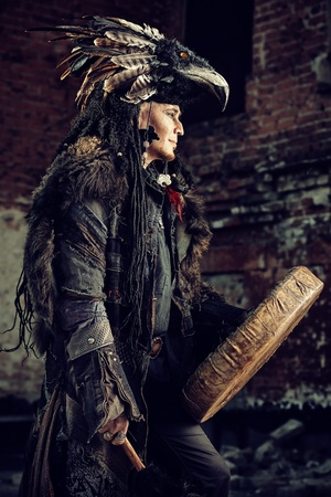 Portrait of a shaman dancing with a drum outdoor.  photo