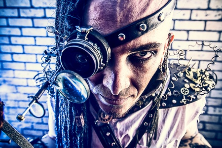 Portrait of a steampunk man with a mechanical devices over brick wall. Stock Photo - 21404964