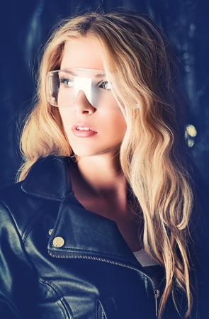 Stunning blonde woman in black leather jacket in the old garage. photo