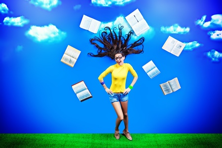 Happy girl student is flying in the sky with her books.  photo