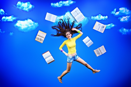 flying woman: Happy girl student is flying in the sky with her books.