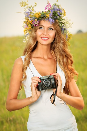Portrait of a romantic smiling young woman in a circlet of flowers standing with her old camera outdoors. Stock Photo