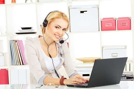 Portrait of smiling young woman operator in headset at office. photo