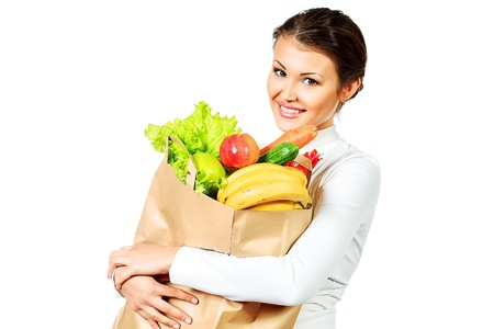 Beautiful young woman holding a bag with fresh fruits and vegetables. Healthy eating. Isolated over white. photo