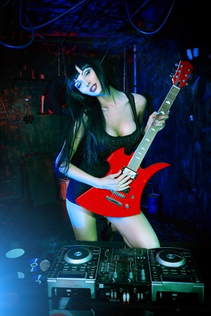Beautiful sexy girl playing electric guitar in the old garage.