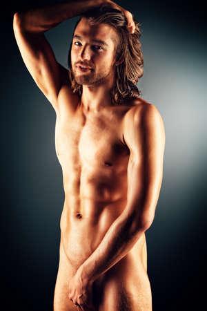 desnudo masculino: Hombre desnudo musculoso sexual que presenta sobre fondo oscuro.