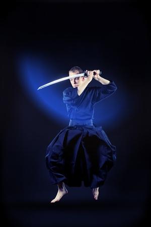 kendo: Handsome young man practicing kendo. Over dark background. Stock Photo