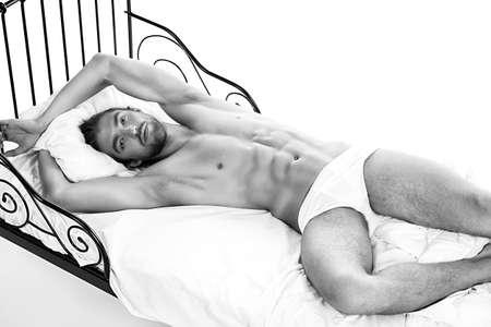 pareja desnuda: Hombre desnudo hermoso que miente en una cama. Aislado en blanco.