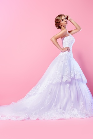 Full length portrait of a beautiful charming bride in a luxurious dress. Over pink background. Stock Photo - 21774320