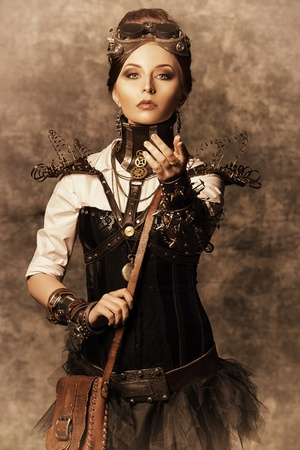 Portrait of a beautiful steampunk woman over grunge background. photo