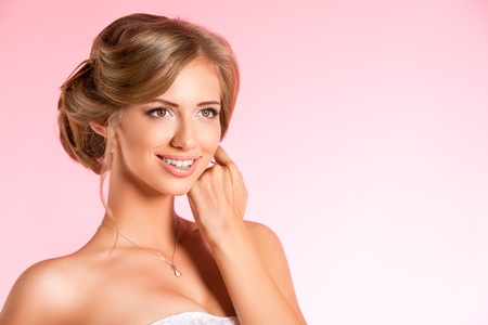 Portrait of a beautiful bride, sweet and sensual. Over pink background. Stock Photo - 21774354