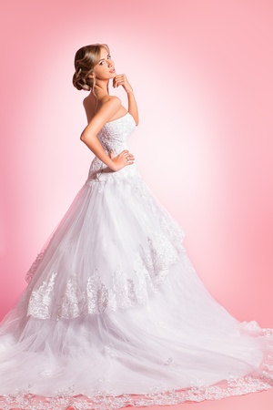 Full length portrait of a beautiful charming bride in a luxurious dress. Over pink background. Stock Photo - 21774357