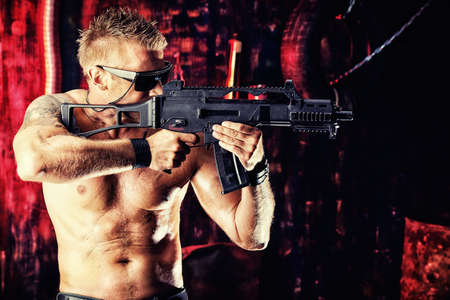 man holding gun: Portrait of a handsome muscular soldier man holding a machine gun. Grunge background.  Stock Photo