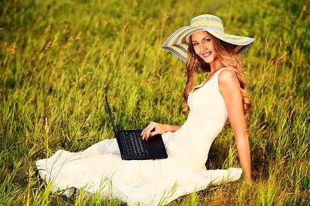 educacion sexual: Joven y bella mujer sonriente sentado con una computadora portátil al aire libre.
