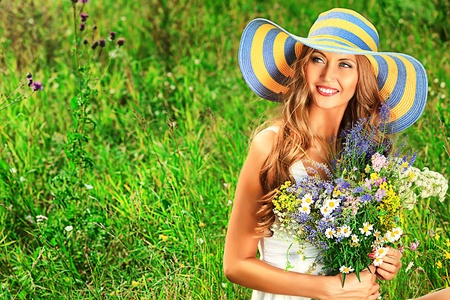 wild hair: Portrait of a romantic smiling young woman with a bouquet of wild flowers outdoors.