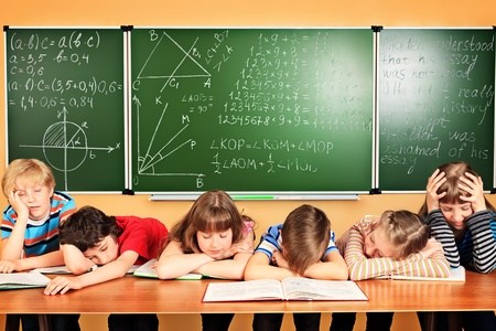 classmates: Group of tired school children at a classroom. Education. Stock Photo