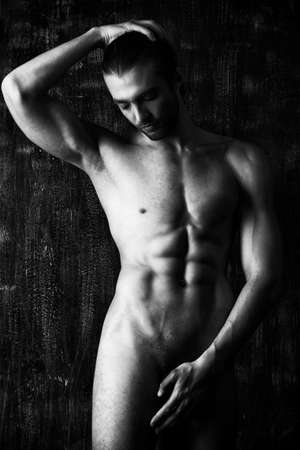 erotic male: Sexual muscular nude man posing over dark background. Stock Photo