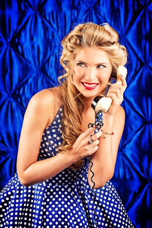 Charming pin-up woman with retro hairstyle and make-up talking on the phone. Stock Photo - 21937574