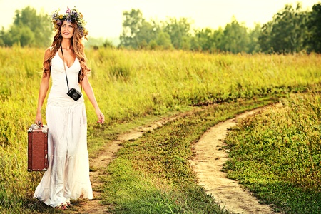 circlet: Romantic smiling young woman in a circlet of flowers goes on a country road with her old camera and suitcase. Stock Photo