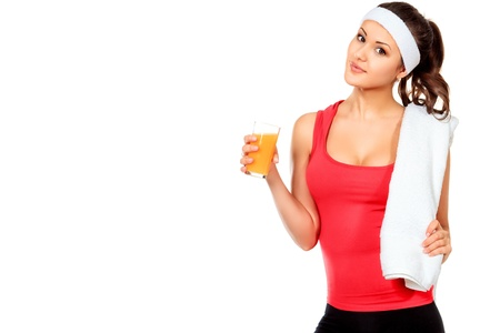 over eating: Sportive young woman standing after training with orange juice. Healthy eating. Isolated over white. Stock Photo
