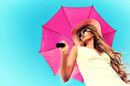 fashion clothing: Beautiful young woman in elegant hat and sunglasses holding umbrella over sky.
