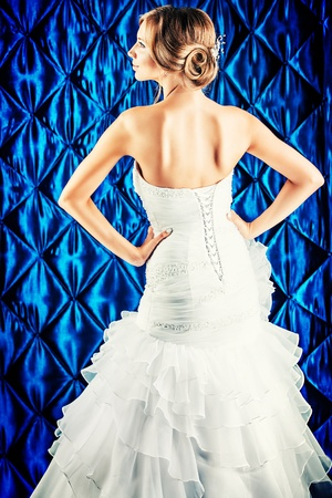 Beautiful charming bride in a luxurious dress standing with her back.  photo