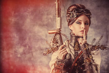 subculture: Portrait of a beautiful steampunk woman holding a gun over grunge background.