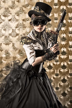 Portrait of a beautiful steampunk woman holding a gun over vintage background. photo