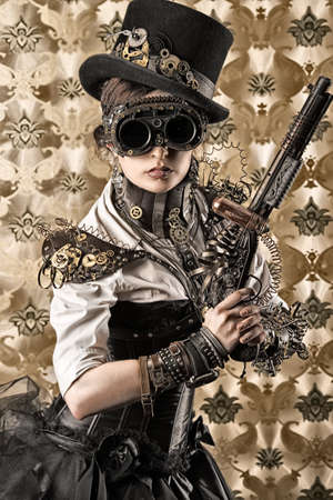 mujer con pistola: Retrato de una mujer hermosa del steampunk con una pistola sobre fondo de cosecha.