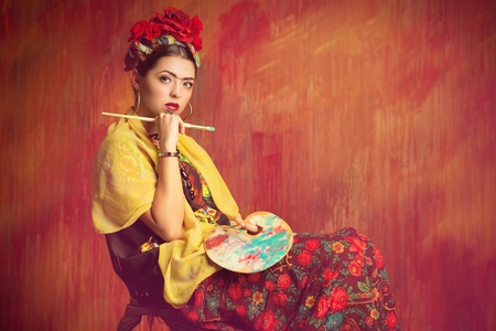 Portrait of an old-fashioned woman painter holding a palette and brush.  photo