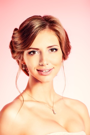 Portrait of a beautiful bride, sweet and sensual. Over pink background. photo