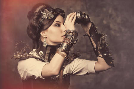 Portrait of a beautiful steampunk woman looking through the binoculars over grunge background. photo