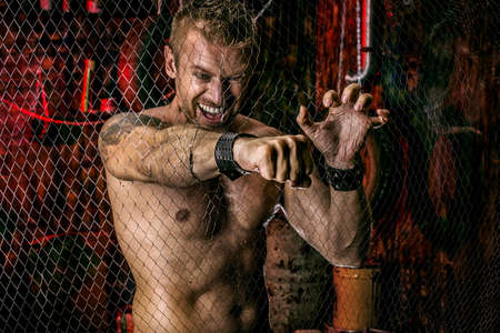 brawny: Handsome muscular man breaks through the metal mesh with a fist. Grunge background.