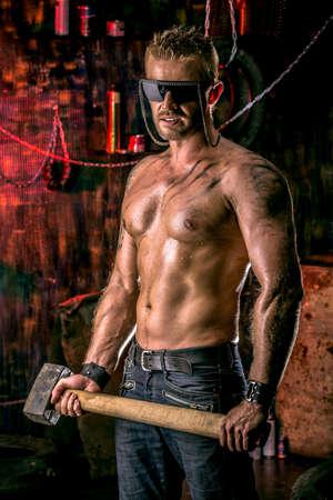 violence in the workplace: Hombre musculoso guapo con martillo de trabajo en el garaje de edad.