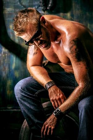violence in the workplace: Retrato de un hombre musculoso guapo en el viejo garaje.