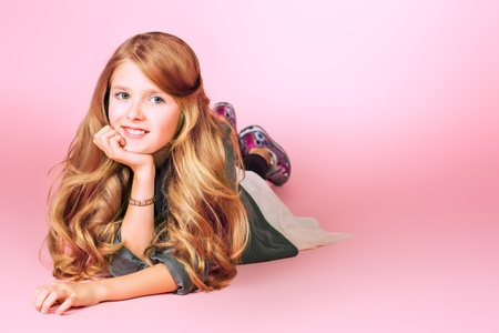 Portrait of a beautiful ten years girl smiling at camera. Pink background. photo
