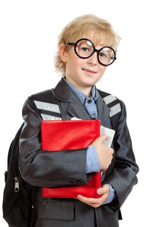 Portrait of a happy schoolboy with backpack and book. Isolated over white background. photo