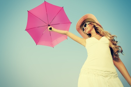 Beautiful young woman in elegant hat and sunglasses holding umbrella over sky. photo