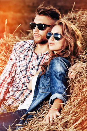 Beautiful young couple in casual clothes sitting together in haystack.