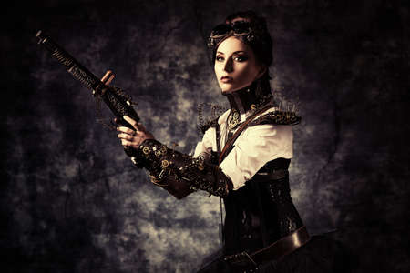 Portrait of a beautiful steampunk woman holding a gun over grunge background. Stock Photo - 22241239