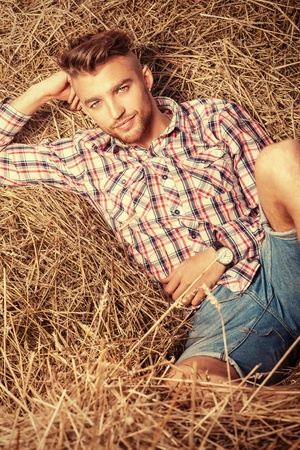Handsome young man lying in haystack. photo