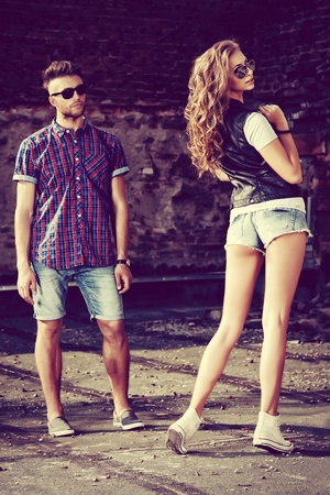 Couple of young people in jeans clothes posing outdoors over brick wall. photo